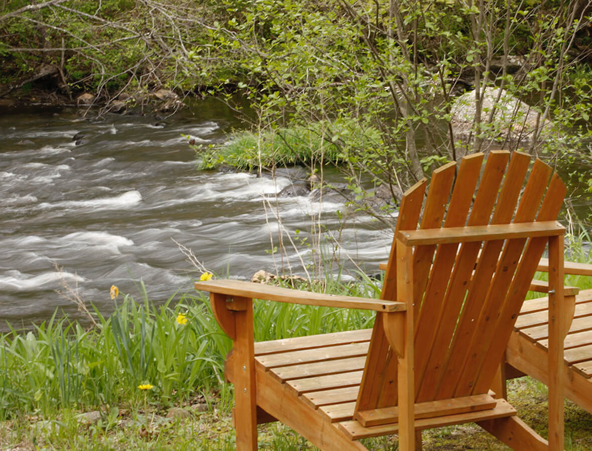 Image of Adirondack chairs alongside river
