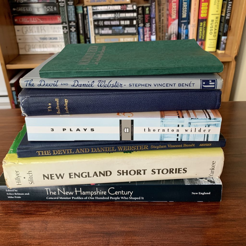 Stack of New Hampshire-related books on table in front of bookshelf